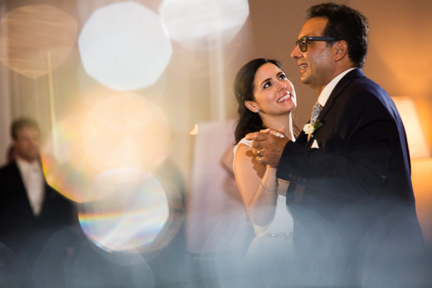 Bride smiles at her father during father daughter dance at her wedding
