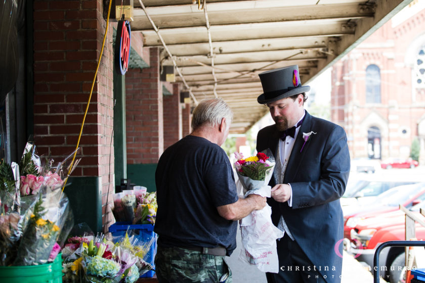 Groom in top hat buys flowers for his bride in the Strip District