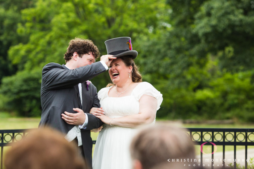 Groom puts his top hat on his bride during their wedding ceremony