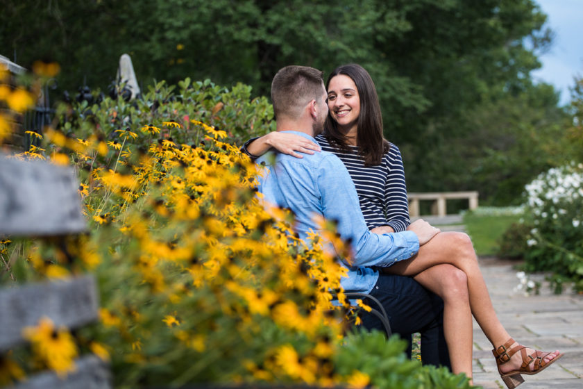 Engaged couple snuggling by black eyed susans