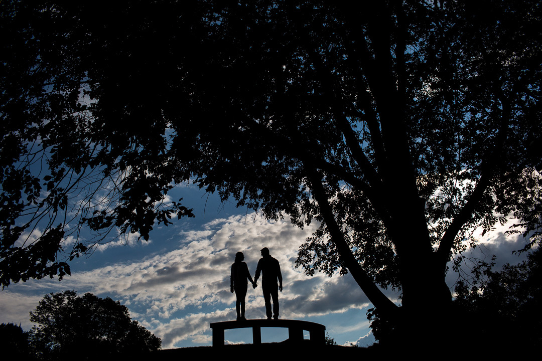 Silhouetted couple on a bench in Mellon Park