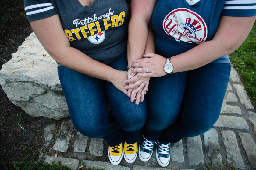 Women in Pittsburgh Steelers and New York Yankees T Shirts sitting together holding hands