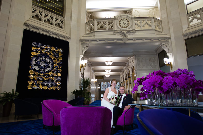 Bride and Groom in lobby of Pittsburgh Union Trust Building with purple chairs