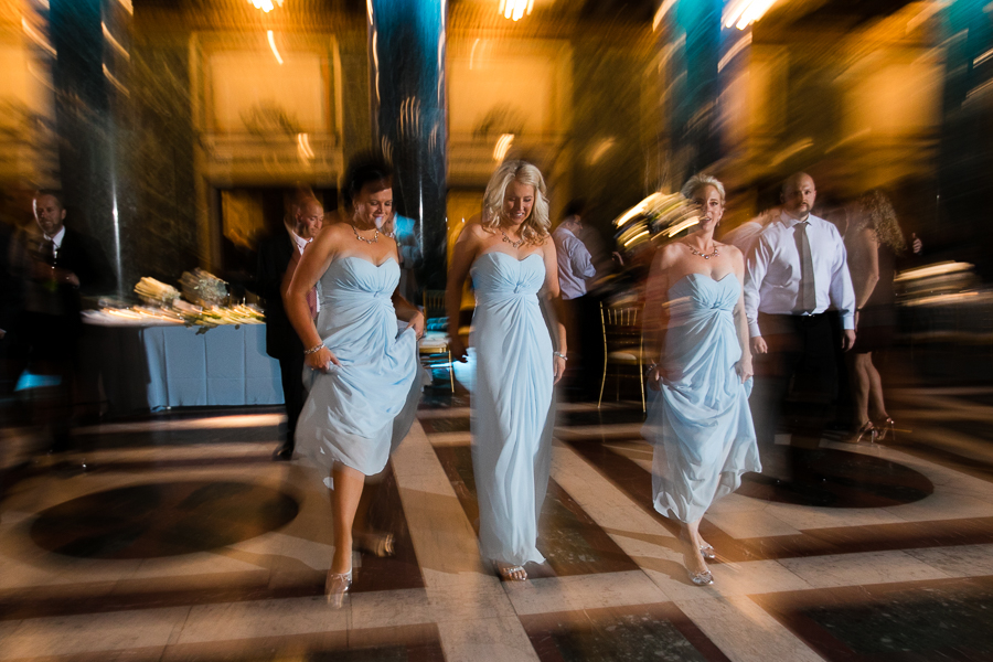 Bridesmaids in light blue dresses dancing at the Carnegie Music Hall Foyer