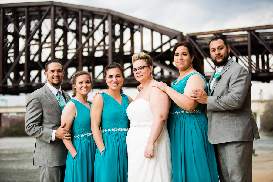 Bride with Bridesmaids in Teal Dresses and Groomsmen with Gray Suits and Teal Tiles