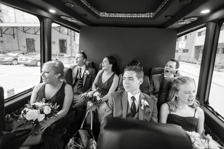 Bridal party singing in the rain on the shuttle van