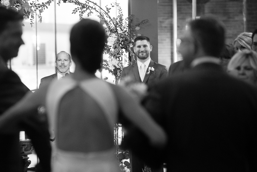 Groom smiling at his bride as she walks down the aisle at wedding ceremony at Heinz History Center Library