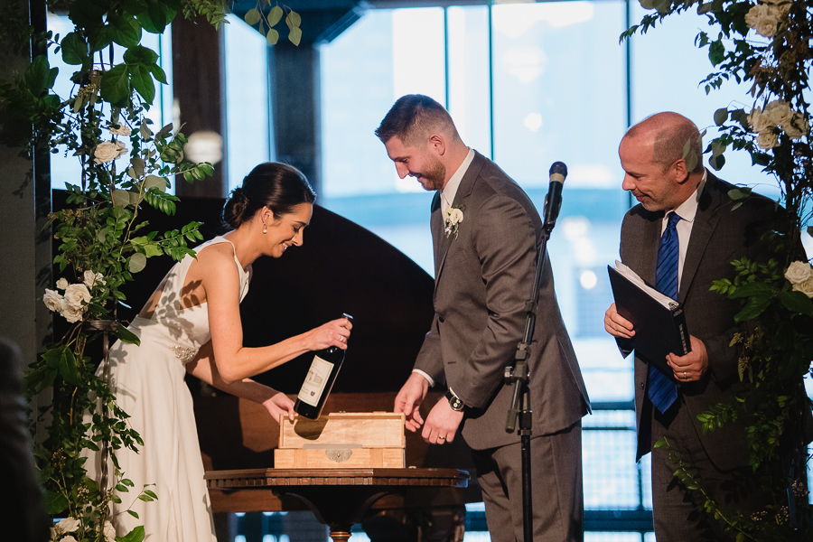 Bride and groom putting wine into wine box during their wedding ceremony