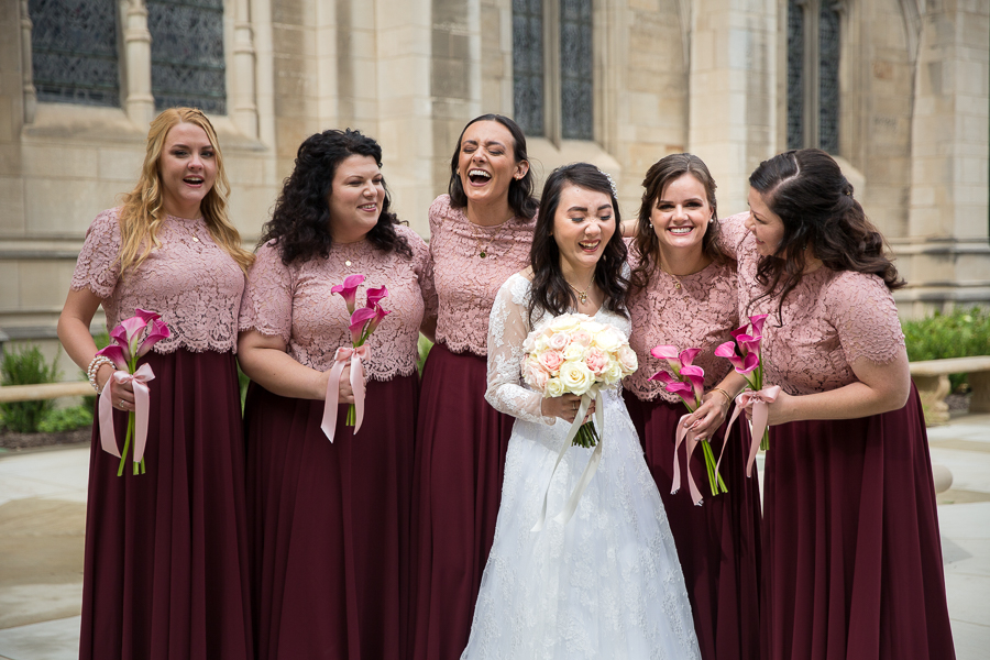 Bride and bridesmaids laughing in the garden outside Heinz Chapel