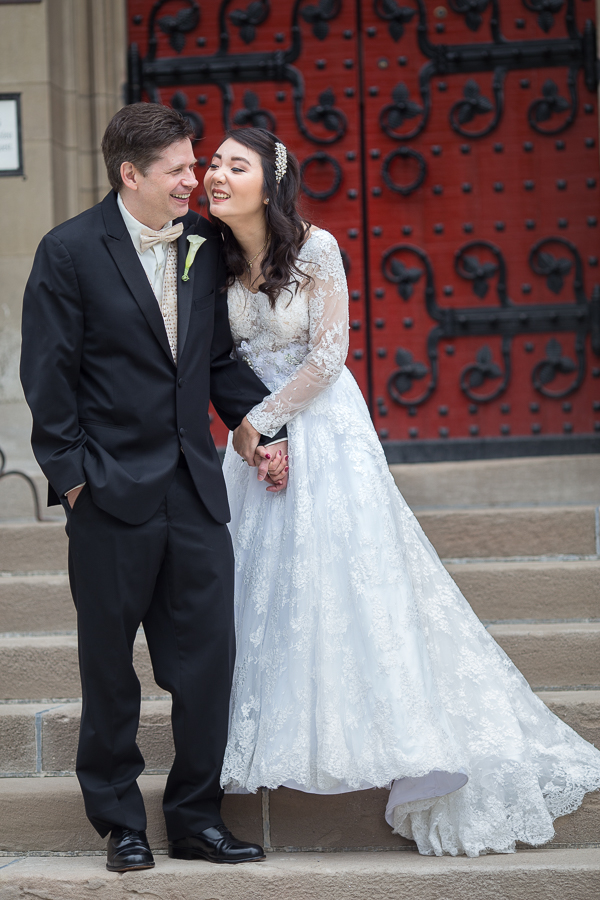 Bride and groom in front of Heinz Chapel's famous red doors