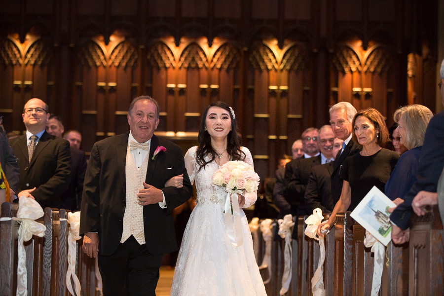 Bride and her dad walking down the aisle of her wedding ceremony