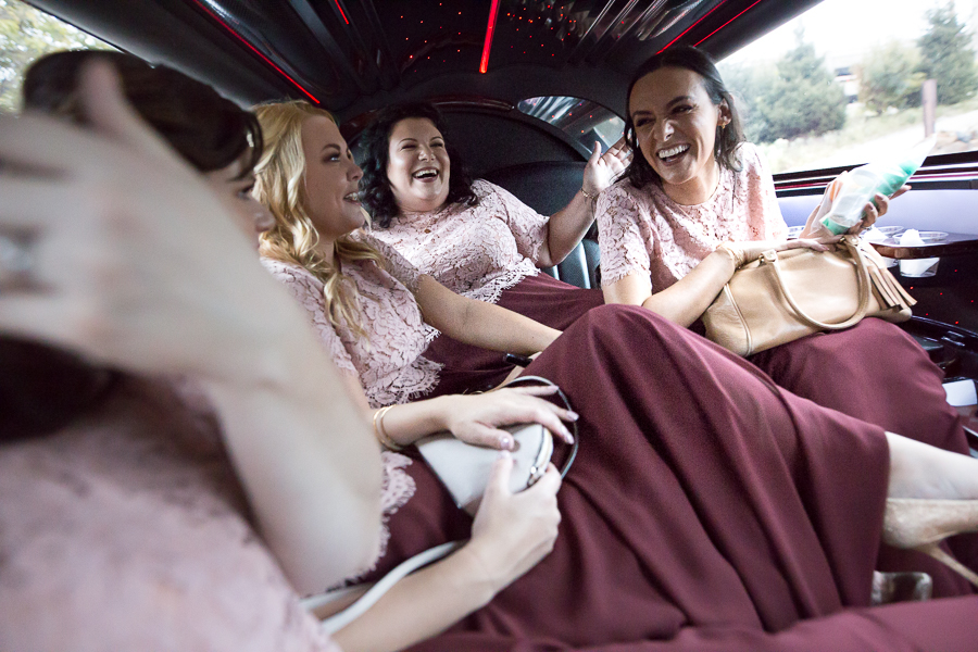 Bridesmaids laughing in the limo