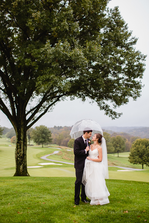 Bride and Groom in the Rain Under a Clear Umbrella at Edgewood Country Club