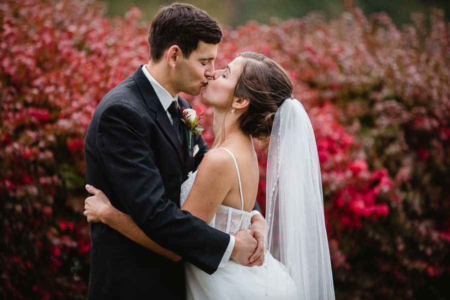 Bride and Groom Kissing in front of Red Shrub atEdgewood Country Club Wedding