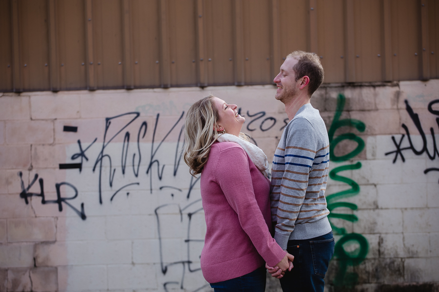 Engagement photos in front of graffiti wall in Pittsburgh's strip district