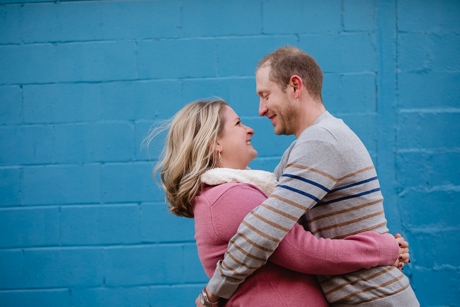 Engaged Couple in front of Blue Wall in Pittsburgh's Strip District