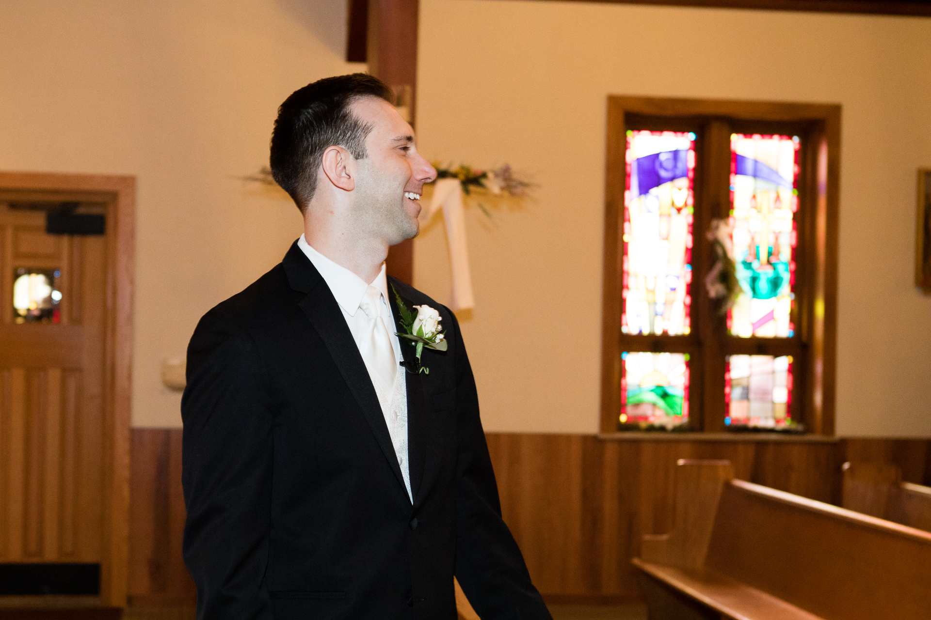 Groom smiling at bride walking down the aisle