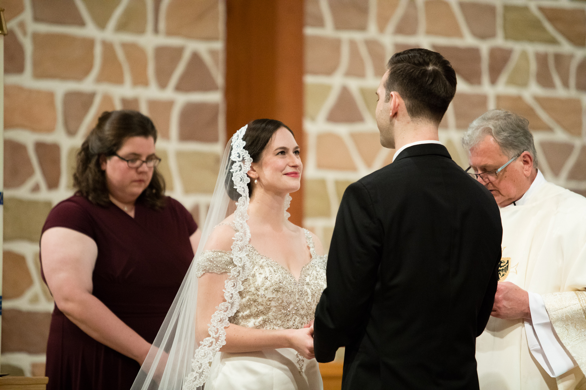 Bride with mantilla saying vows at wedding ceremony