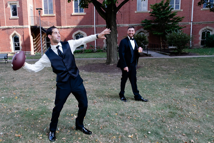 Groom and groomsman playing football before the wedding